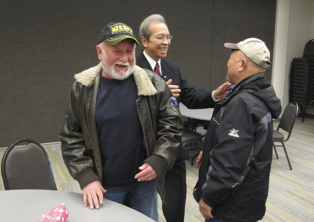 In this Dec. 15, 2017 photo, Tri Phan, center, greets two well-wishers at his retirement party at Lutheran Social Services in Fargo, N.D. Phan worked ...