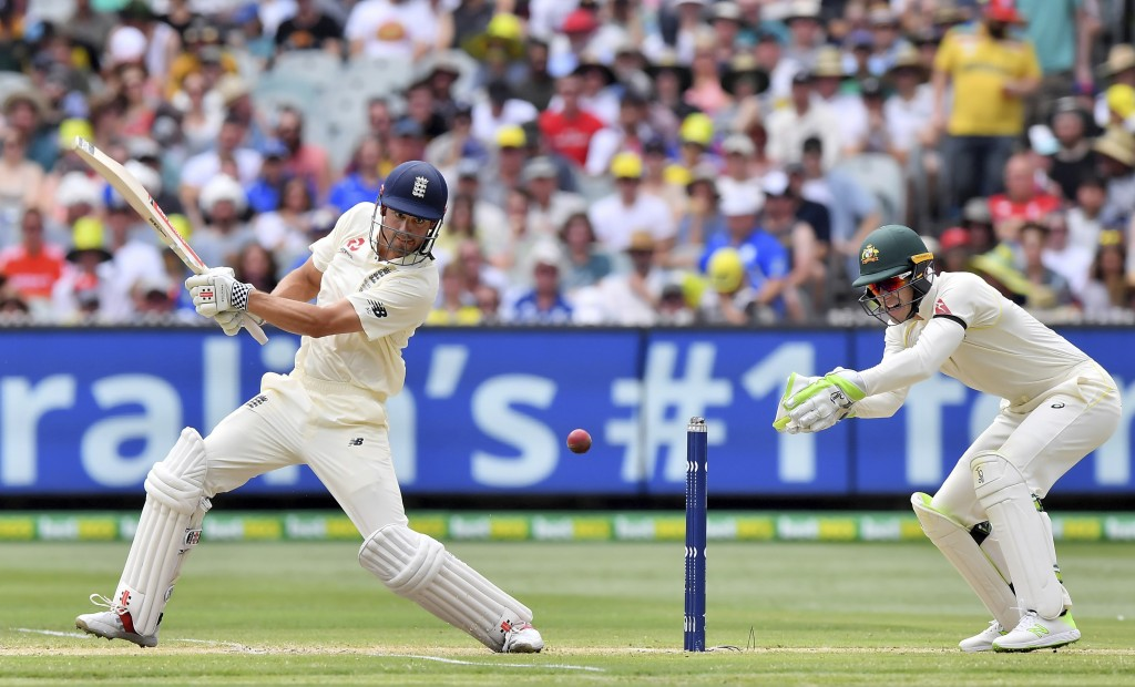 England's Alastair Cook, left, cuts the ball in front of Australia's Tim Paine during the third day of their Ashes cricket test match in Melbourne, Au...