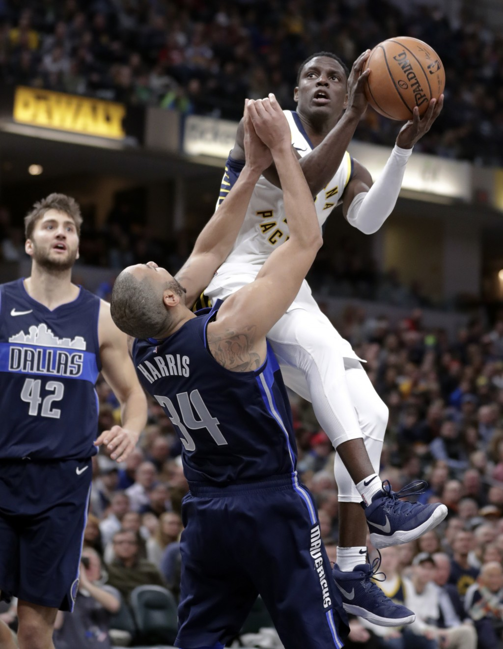 Indiana Pacers guard Darren Collison (2) shoots over Dallas Mavericks guard Devin Harris (34) during the second half of an NBA basketball game in Indi...