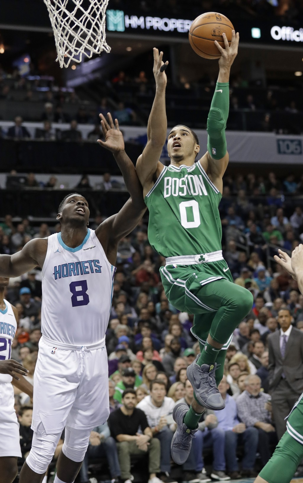 Boston Celtics' Jayson Tatum (0) drives past Charlotte Hornets' Johnny O'Bryant III (8) during the first half of an NBA basketball game in Charlotte, ...