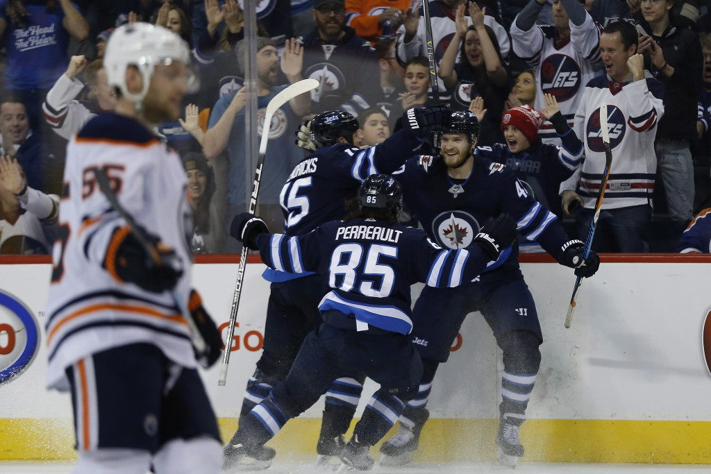 Winnipeg Jets' Matt Hendricks (15), Mathieu Perreault (85) and Joel Armia (40) celebrate Armia's goal against the Edmonton Oilers during the second pe...