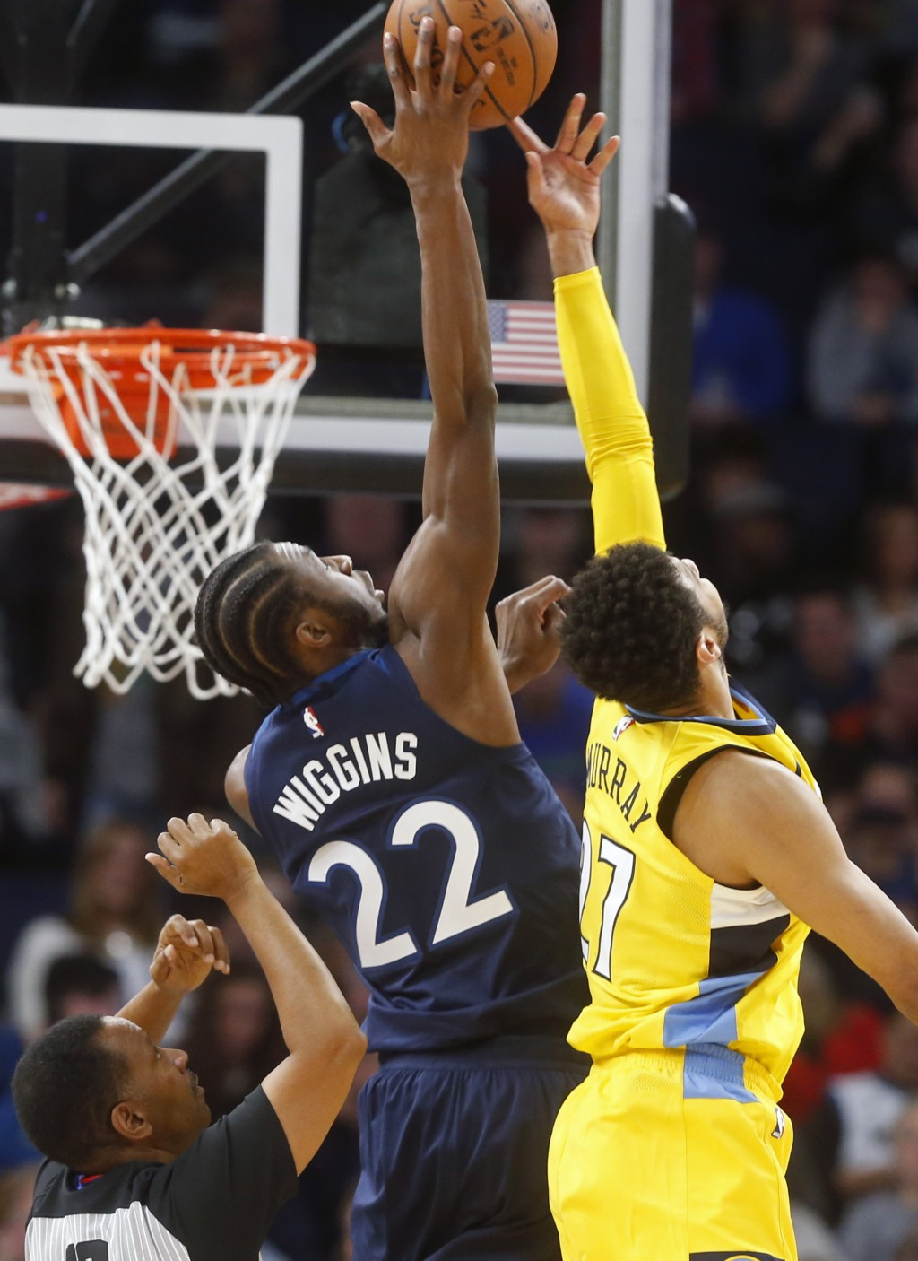 Minnesota Timberwolves' Andrew Wiggins, left, outreaches Denver Nuggets' Jamal Murray as he shoots in the first half of an NBA basketball game, Wednes...