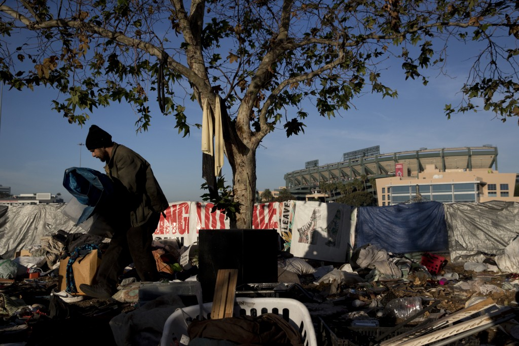 Homeless Junior Sanchez, 29, carries a tarp he found in a pile of trash in a homeless encampment on the Santa Ana River trail near Angel Stadium Satur...