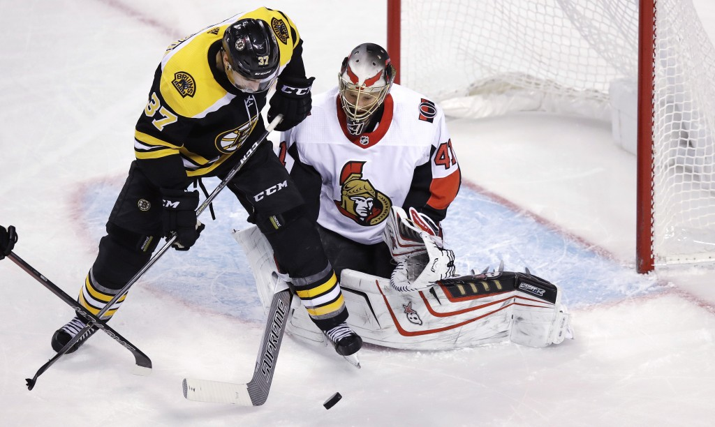 Ottawa Senators goalie Craig Anderson, right, tries to poke the puck away from Boston Bruins center Patrice Bergeron (37) during the third period of a...