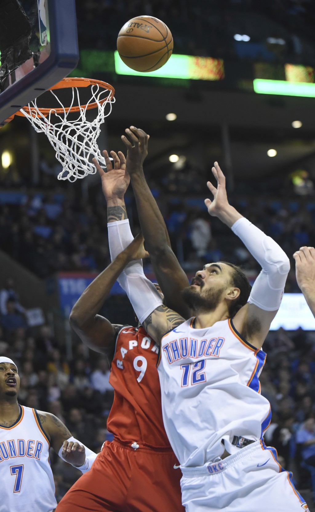 Oklahoma City Thunder's Steven Adams (12) goes up for a rebound next to Toronto Raptors' Serge Ibaka during the first quarter of an NBA basketball gam...