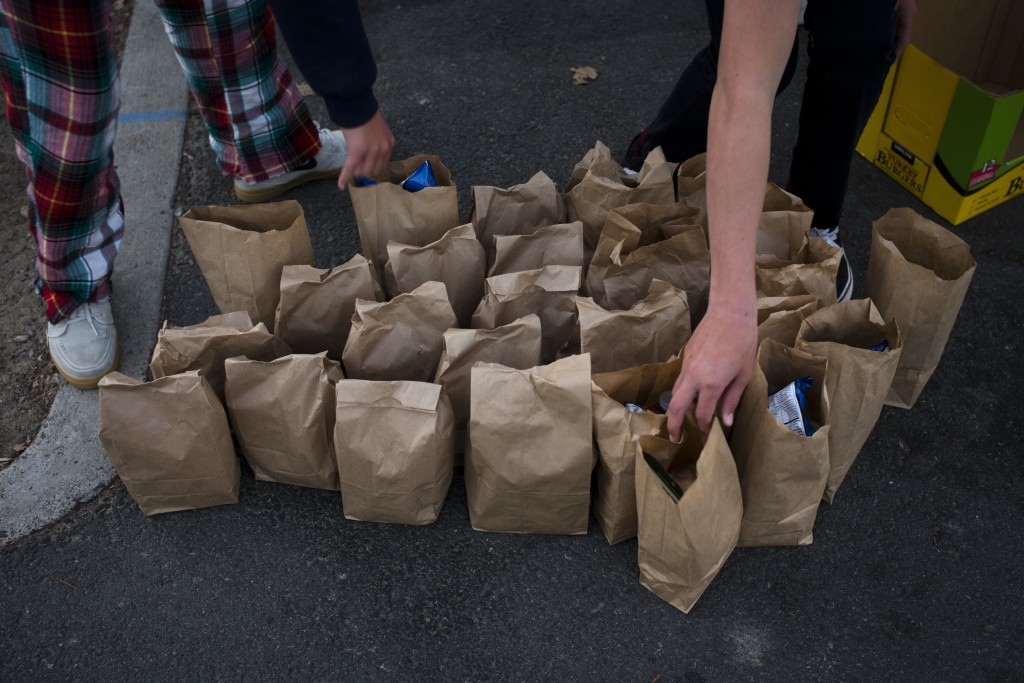 Young volunteers from Lion's Heart, a non-profit community service organization, prepare sack lunches for homeless people Thursday, Dec. 21, 2017, in ...