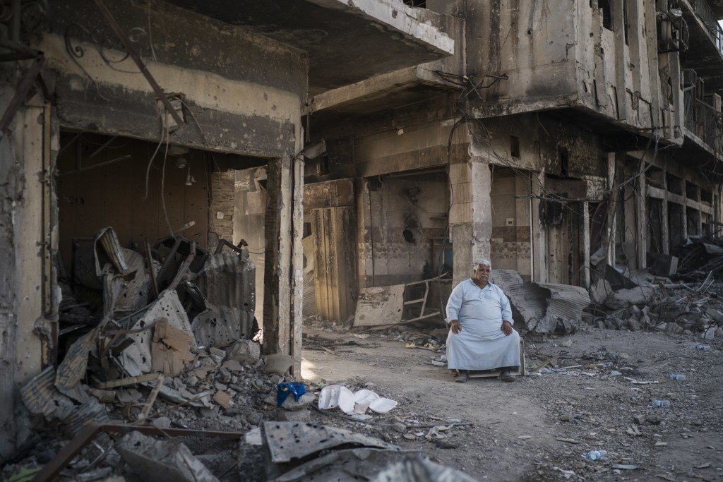 In this Nov. 18, 2017 photo, shop owner Abu Azar sits outside a destroyed bazaar in the Old City of Mosul, Iraq. The cost to rebuild after driving out...