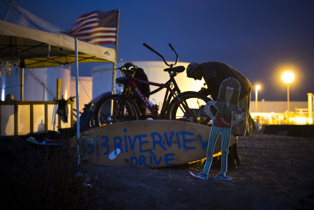 Homeless Lawrence Melvin, 50, looks at his bike next to a surfboard bearing a mock street address on the Santa Ana River trail Sunday, Dec. 10, 2017, ...