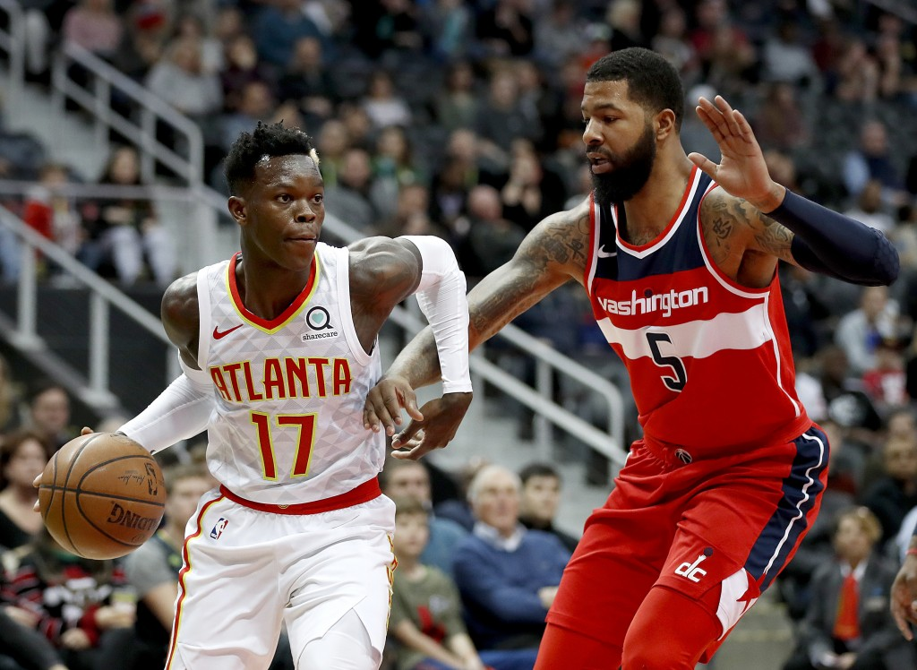 Atlanta Hawks' Dennis Schroder, left, of Germany, dribbles against Washington Wizards' Markieff Morris in the first quarter of an NBA basketball game ...