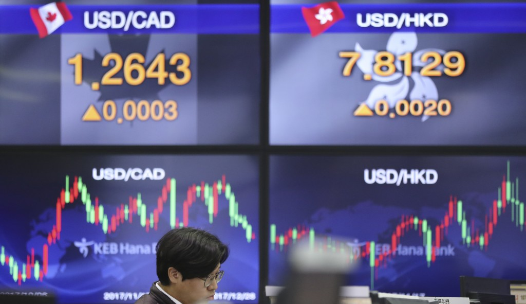 A currency trader watches monitors near the screens showing the foreign exchange rates at the foreign exchange dealing room in Seoul, South Korea, Thu...