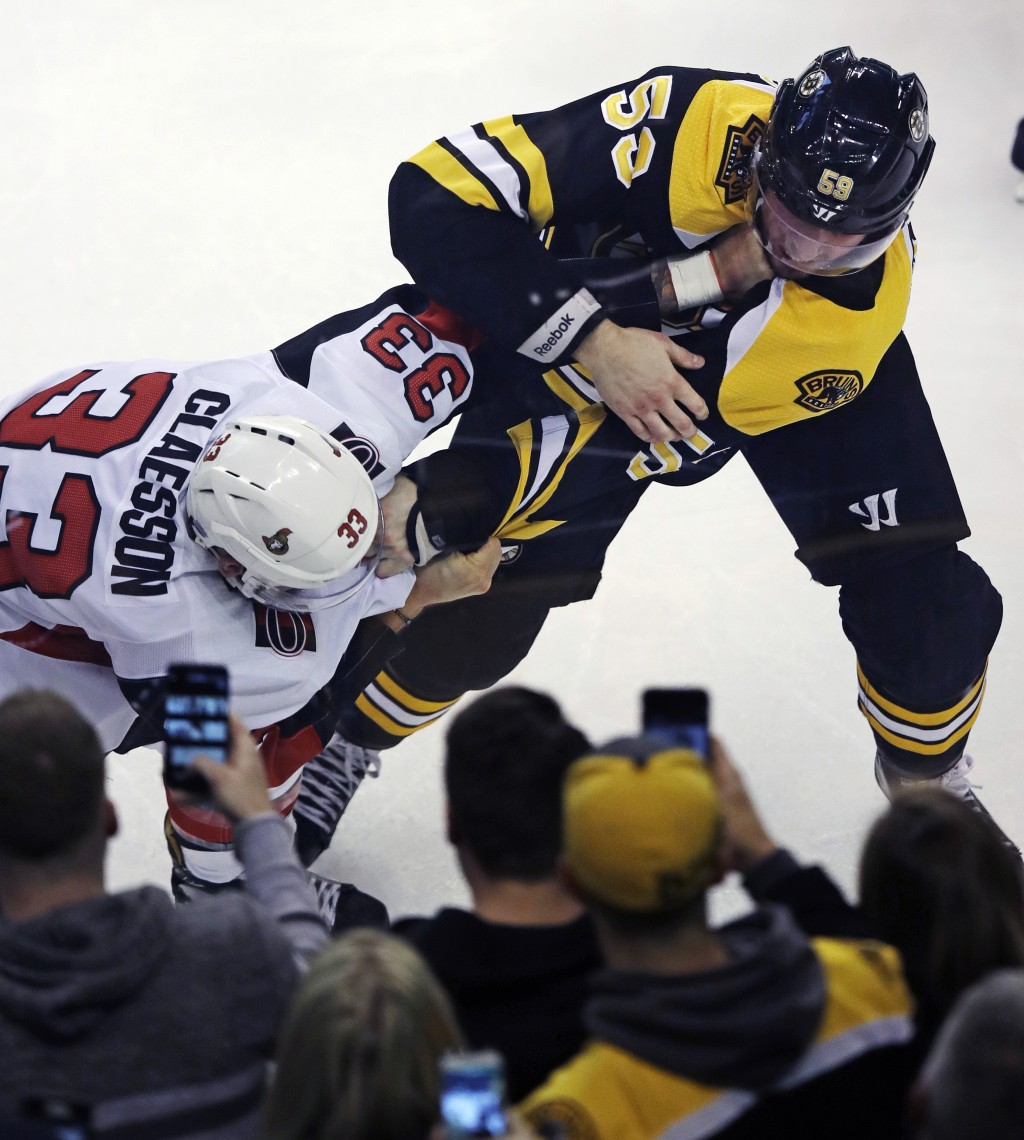 Boston Bruins center Tim Schaller (59) and Ottawa Senators defenseman Fredrik Claesson (33) fight in front of fans during the first period of an NHL h...