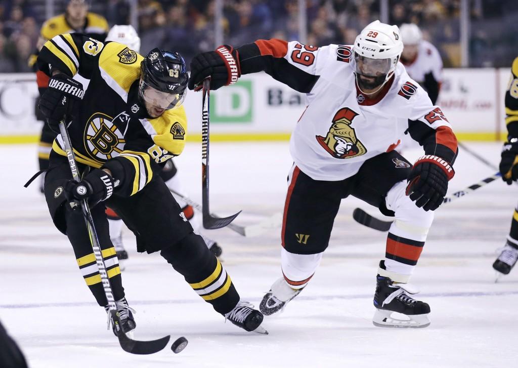 Boston Bruins left wing Brad Marchand, left, breaks towards the net as Ottawa Senators defenseman Johnny Oduya (29) keeps close during the second peri...