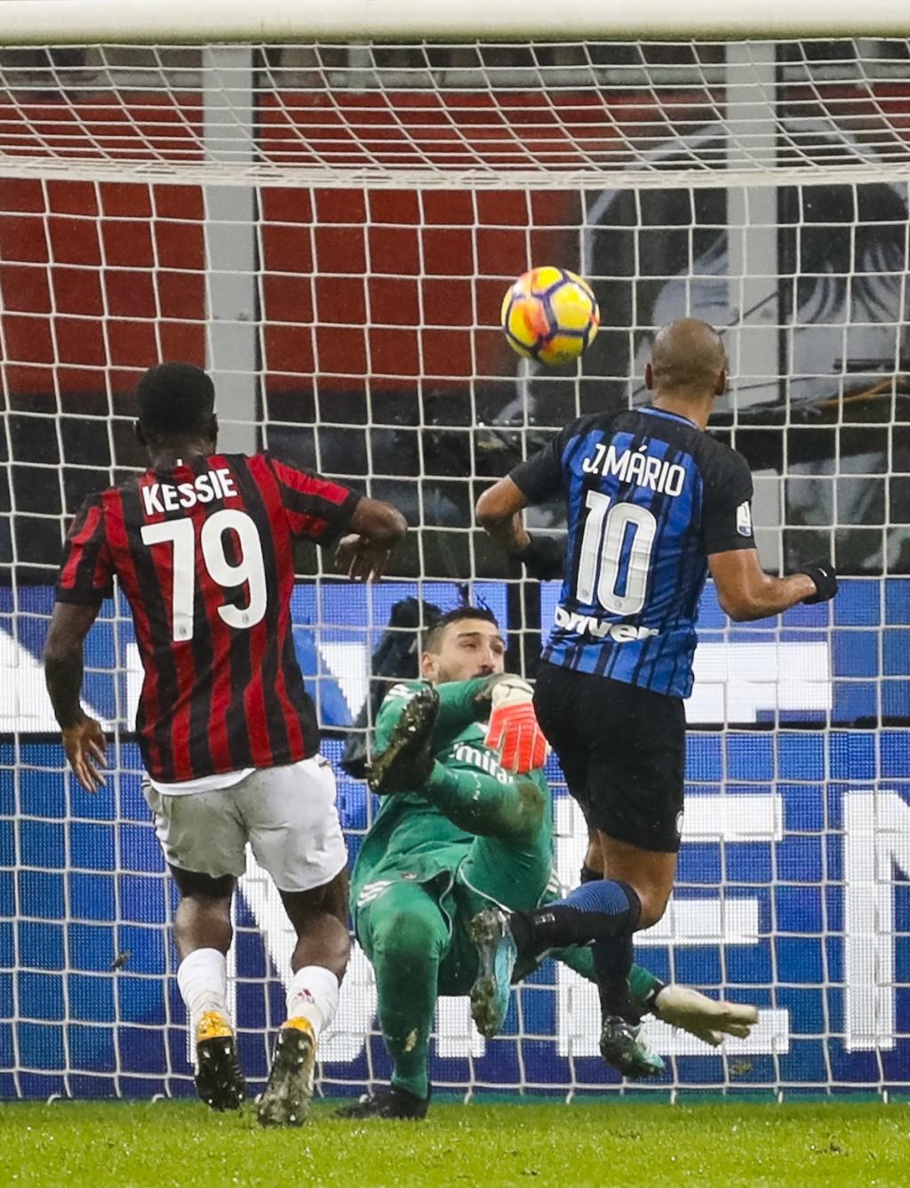 AC Milan goalkeeper Antonio Donnarumma, center, blocks a ball shot by Inter Milan's Joao Mario, right, as AC Milan's Franck Kessie defends during an I...
