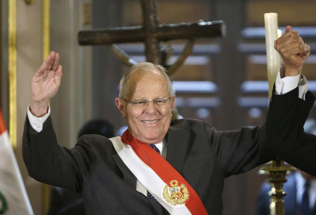 Peru's President Pedro Pablo Kuczynski, raises hands after the swearing in ceremony of the new Interior Minister Vicente Romero, at government palace ...