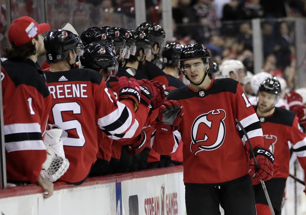 New Jersey Devils center Nico Hischier, right front, of Switzerland, skates by the bench after scoring a goal against the Detroit Red Wings during the...