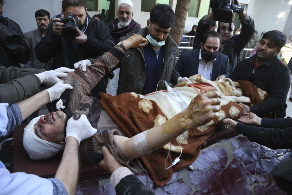 People carry an injured man into the hospital after a suicide attack in Kabul, Afghanistan, Thursday, Dec. 28, 2017. Authorities say two simultaneous ...