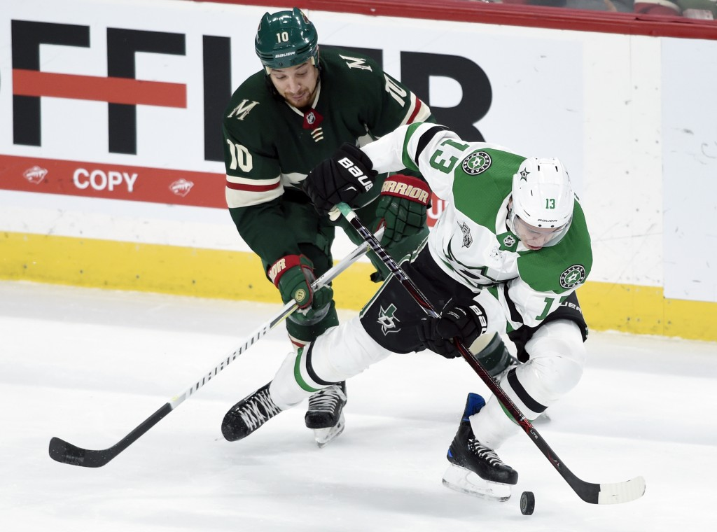 Dallas Stars' Mattias Janmark (13), of Sweden, has the puck against Minnesota Wild's Chris Stewart (10) during the first period of an NHL hockey game ...
