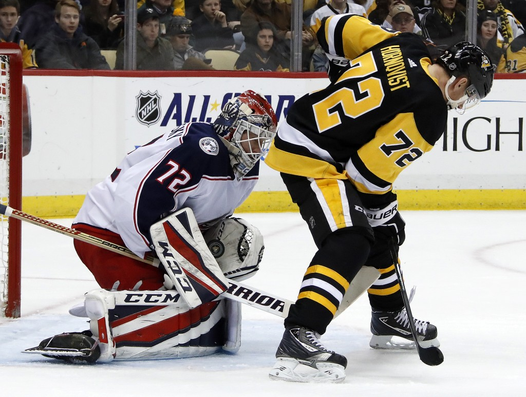 Columbus Blue Jackets goalie Sergei Bobrovsky (72) stops a shot with Pittsburgh Penguins' Patric Hornqvist (72) screening him during the second period...