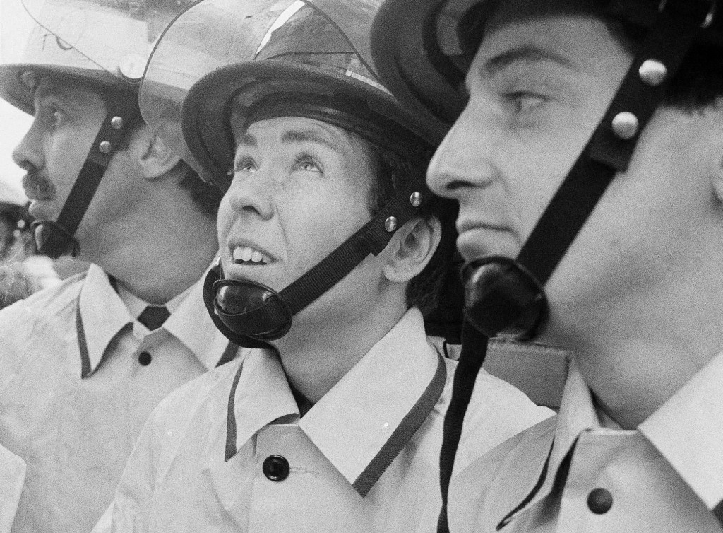 FILE - In this Nov. 6, 1982, file photo, Brenda Berkman, center, watches a demonstration of firefighting techniques with her male colleagues during gr...