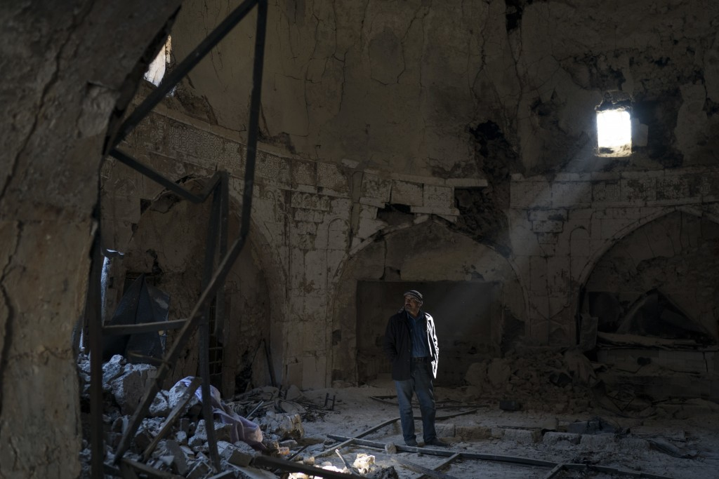 In this Nov. 14, 2017 photo, shop keeper Zyad Mohammed Ali, walks inside a damaged spa in the Old City of Mosul, Iraq. The scope of destruction in the...