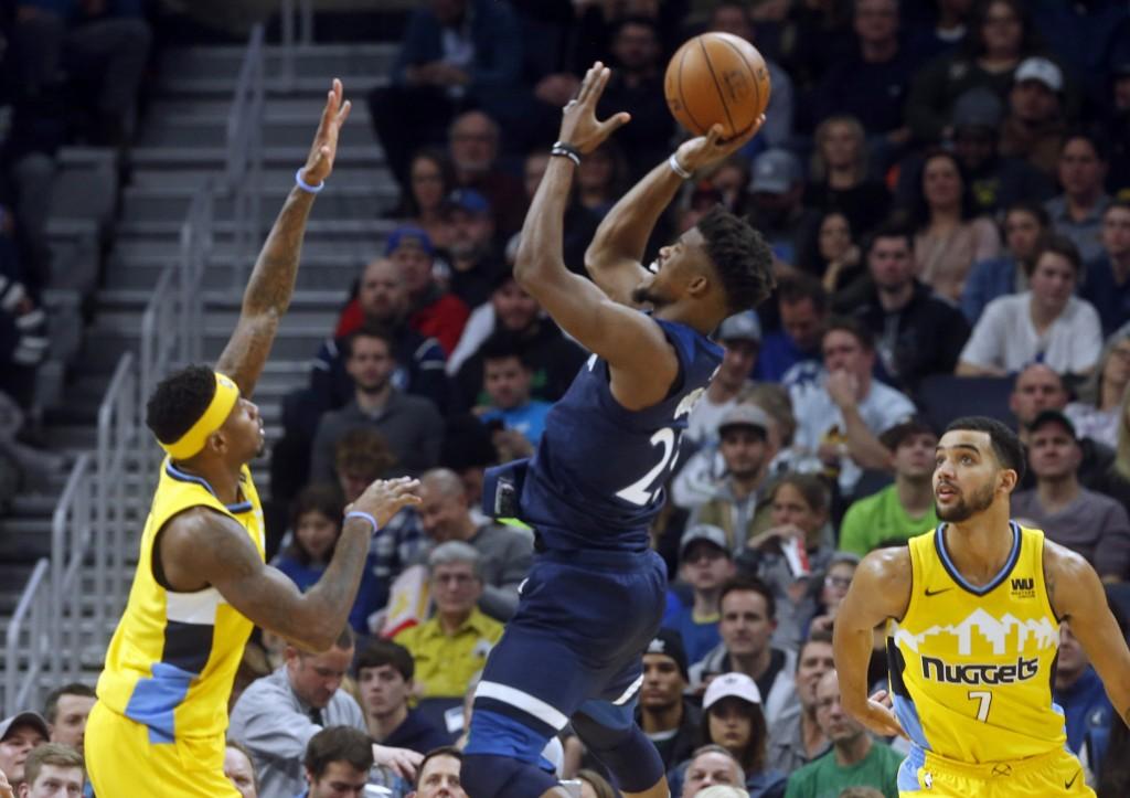 Minnesota Timberwolves' Jimmy Butler, center, shoots over Denver Nuggets' Torrey Craig, left, in the second half of an NBA basketball game Wednesday, ...