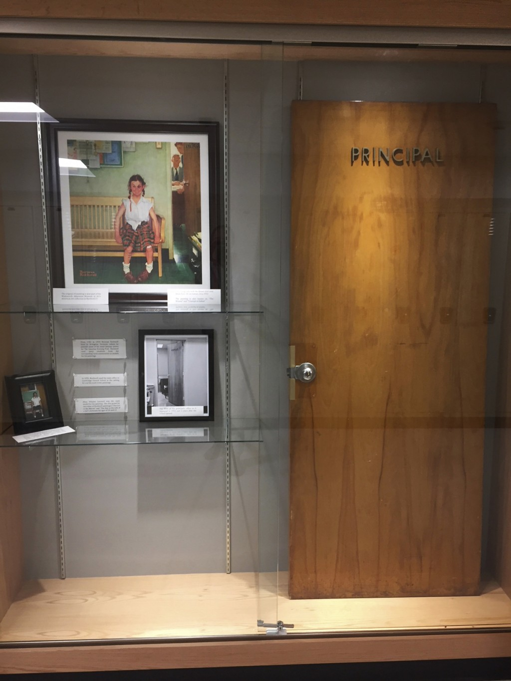 This Dec. 20, 2017, photo provided by Cambridge Central Schools shows a display case with photos, an illustration and the door that was once on the Pr...