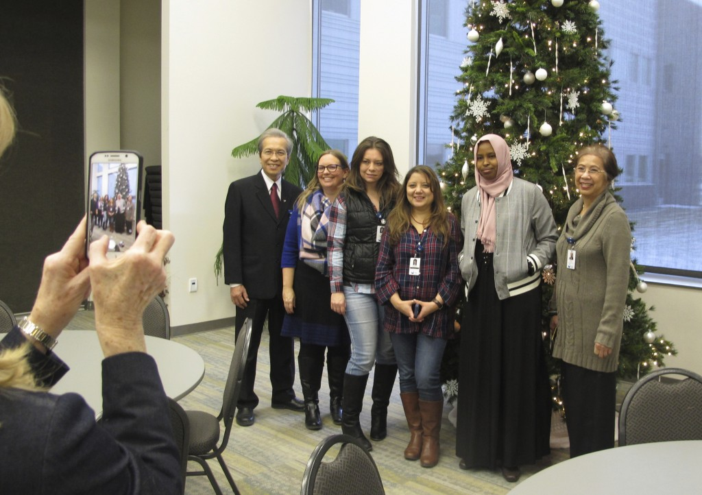 In this Dec. 15, 2017 photo,Tri Phan, left, poses for a photo with staff members at Lutheran Social Services, during his retirement party in Fargo, N....