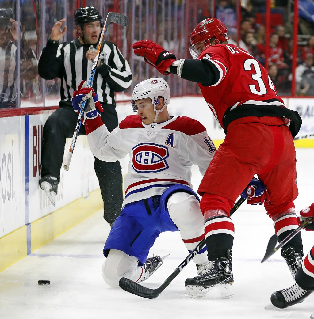 Montreal Canadiens' Brendan Gallagher (11) collides with Carolina Hurricanes' Phillip Di Giuseppe (34) during the first period of an NHL hockey game, ...