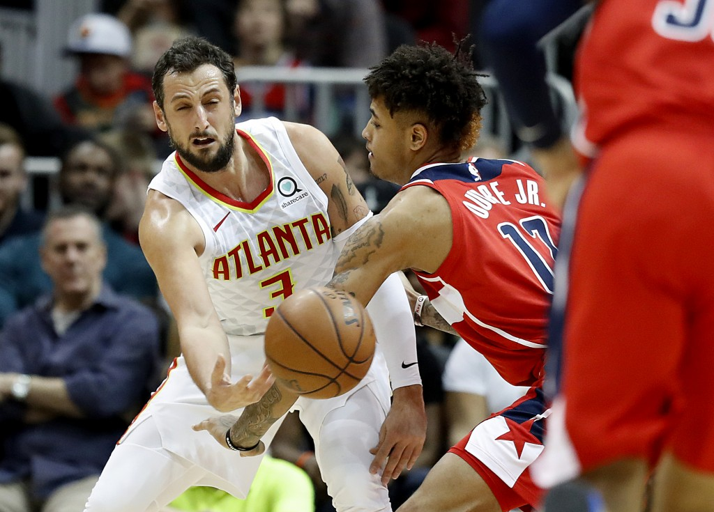 Atlanta Hawks' Marco Belinelli, left, of Italy, passes the ball past Washington Wizards' Kelly Oubre Jr., in the fourth quarter of an NBA basketball g...