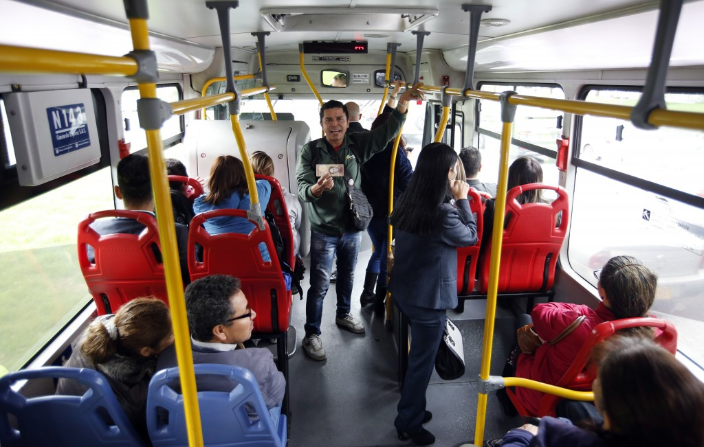 In this Dec. 12, 2017 photo, Venezuelan national Jorge Gutierrez holds a bill of Venezuelan currency as he rides a bus in Bogota, Colombia. Giving awa...