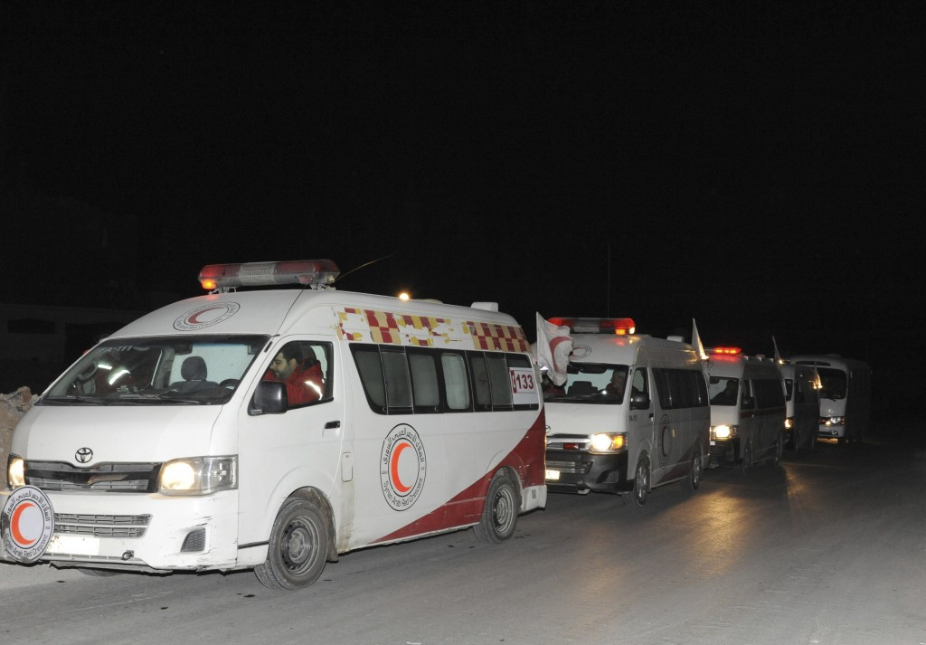 In this photo released by the Syrian official news agency SANA, ambulances of the Syrian Arab Red Crescent queuing during a human mission to evacuate ...