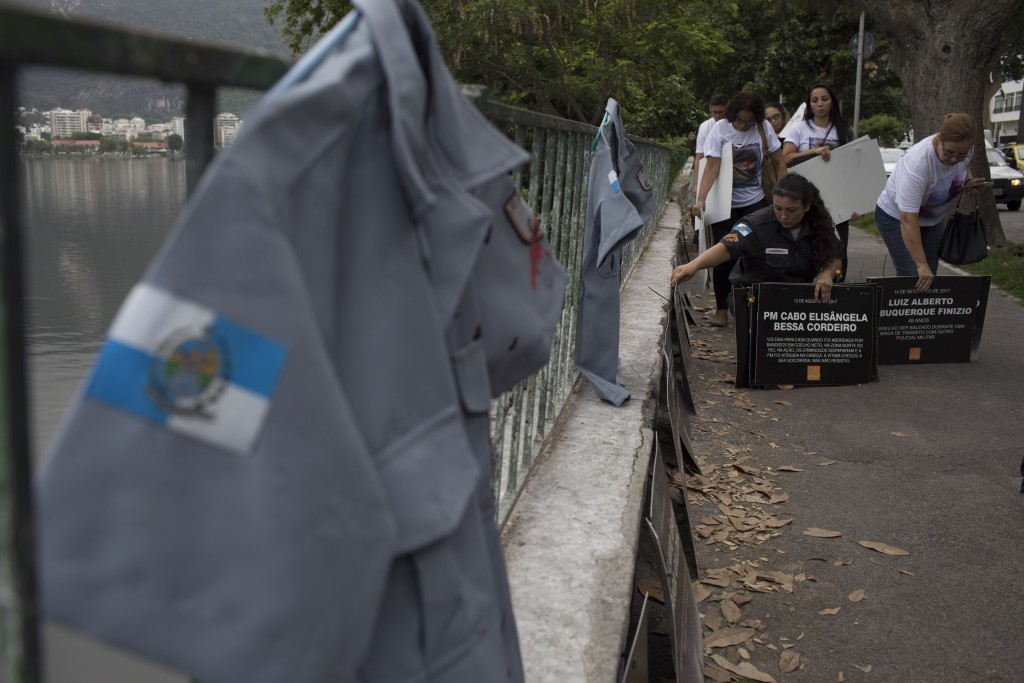 Relatives and friends collect signs with the names of slain police officers written on them, during a demonstration promoted by the NGO Rio de Paz in ...