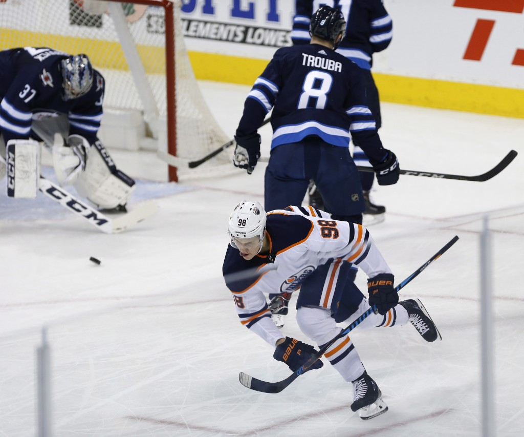 Edmonton Oilers' Jesse Puljujarvi (98) celebrates his goal against Winnipeg Jets goaltender Connor Hellebuyck (37) and Jacob Trouba (8) during the fir...