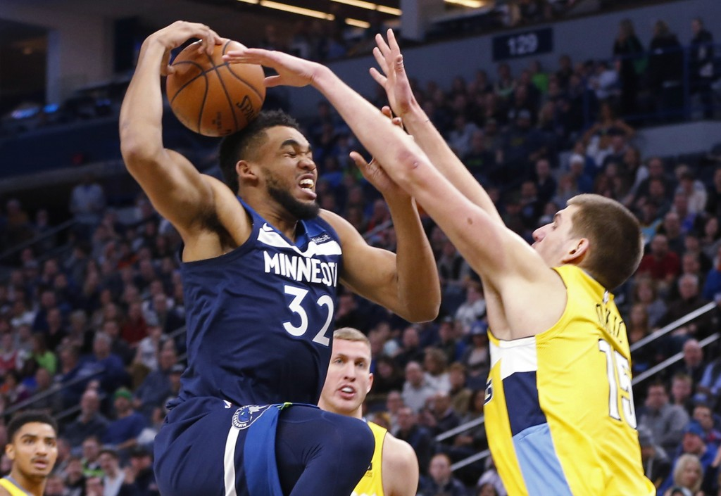 Minnesota Timberwolves' Karl-Anthony Towns, left, attempt a layup before Denver Nuggets' Nikola Jokic of Serbia knocked the ball out of his hand in th...