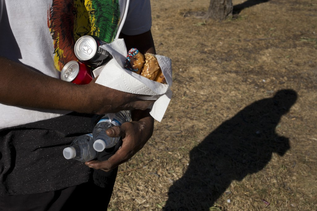 Homeless Jonathan Young, 40, carries donuts, soda and two bottles of water donated to him by church members in a homeless encampment set up on the San...