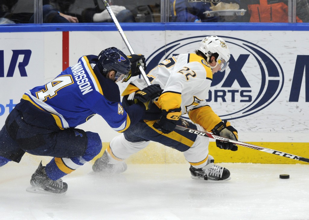 St. Louis Blues' Carl Gunnarsson (4), of Sweden, and Nashville Predators' Kevin Fiala (22), of Switzerland, reach for the puck during the second perio...