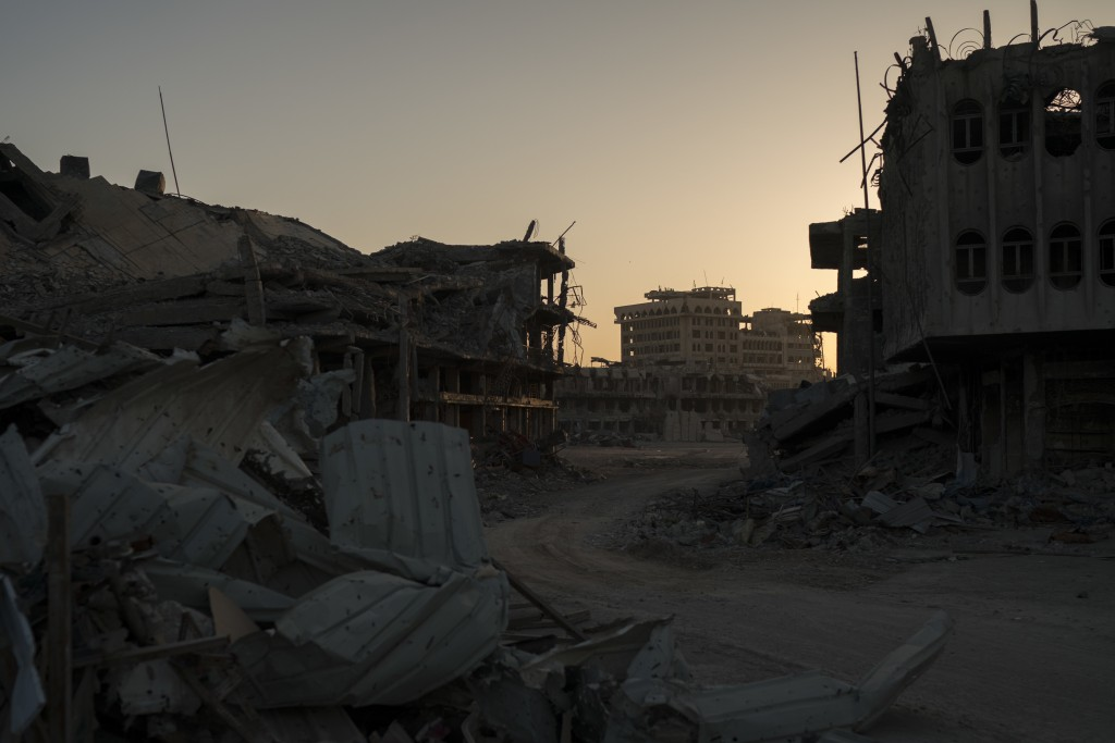 In this Nov. 16, 2017 photo, the sun sets behind damaged buildings in the Old City of Mosul, Iraq. The U.N. estimates around 40,000 homes will need to...