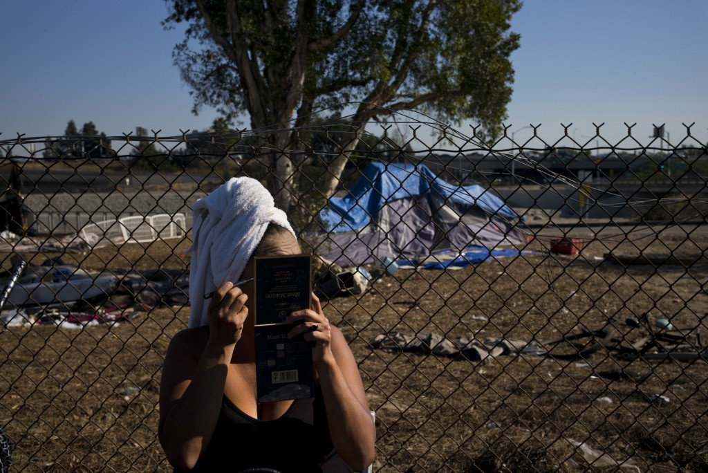 With a towel wrapped around her head, Stella Perez, who is homeless, applies makeup in the parking lot of Angel Stadium after taking a shower in Showe...