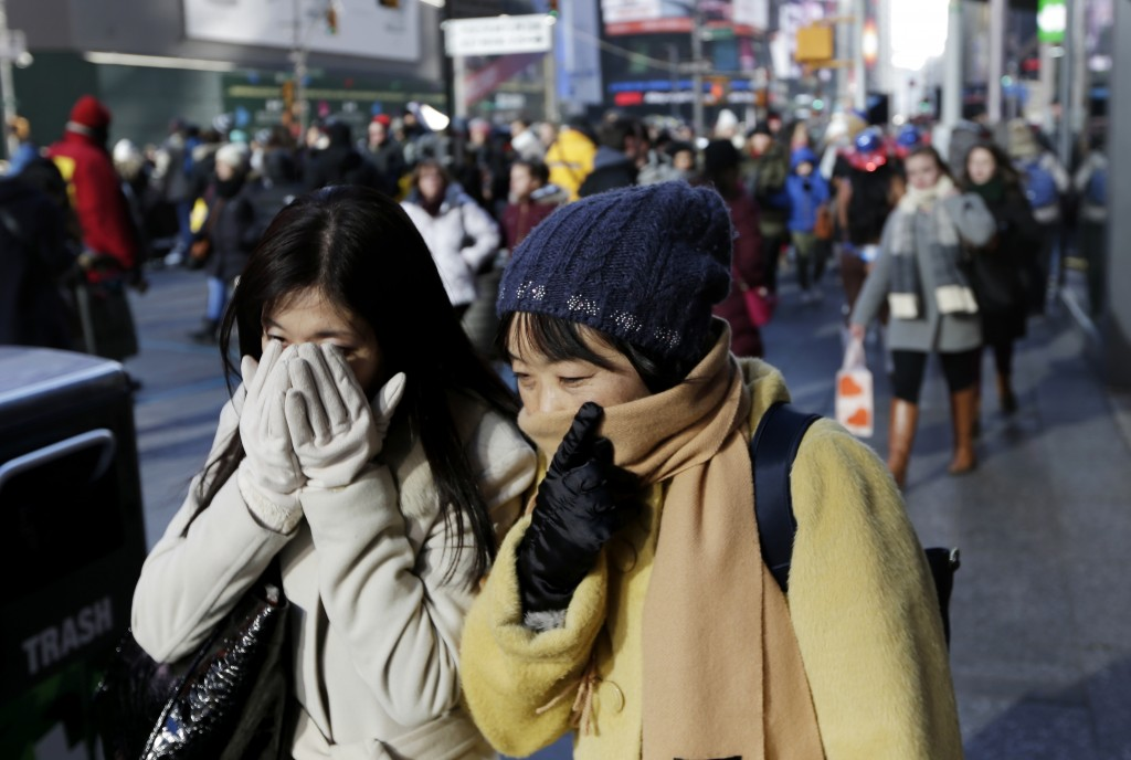 Pedestrians try to keep warm by covering their faces while walking in Times Square, New York, Wednesday, Dec. 27, 2017. Freezing temperatures and belo...