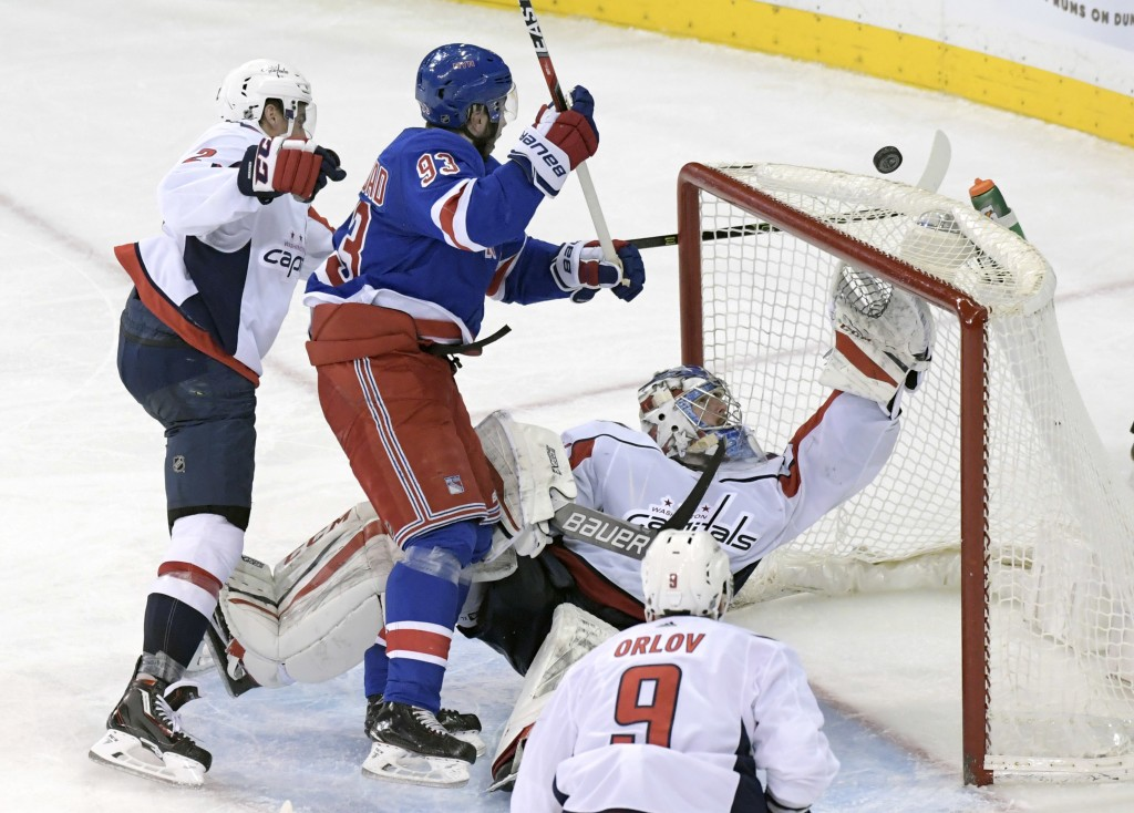 Washington Capitals goalie Philipp Grubauer (31) reaches for the puck which Is on the top of the net as New York Rangers center Mika Zibanejad (93) sk...