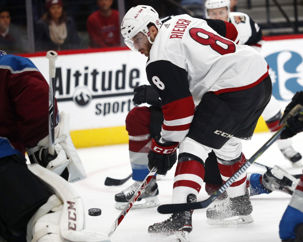 Arizona Coyotes right wing Tobias Rieder, right, of Germany, redirects a shot toward Colorado Avalanche goalie Semyon Varlamov, of Russia, in the seco...