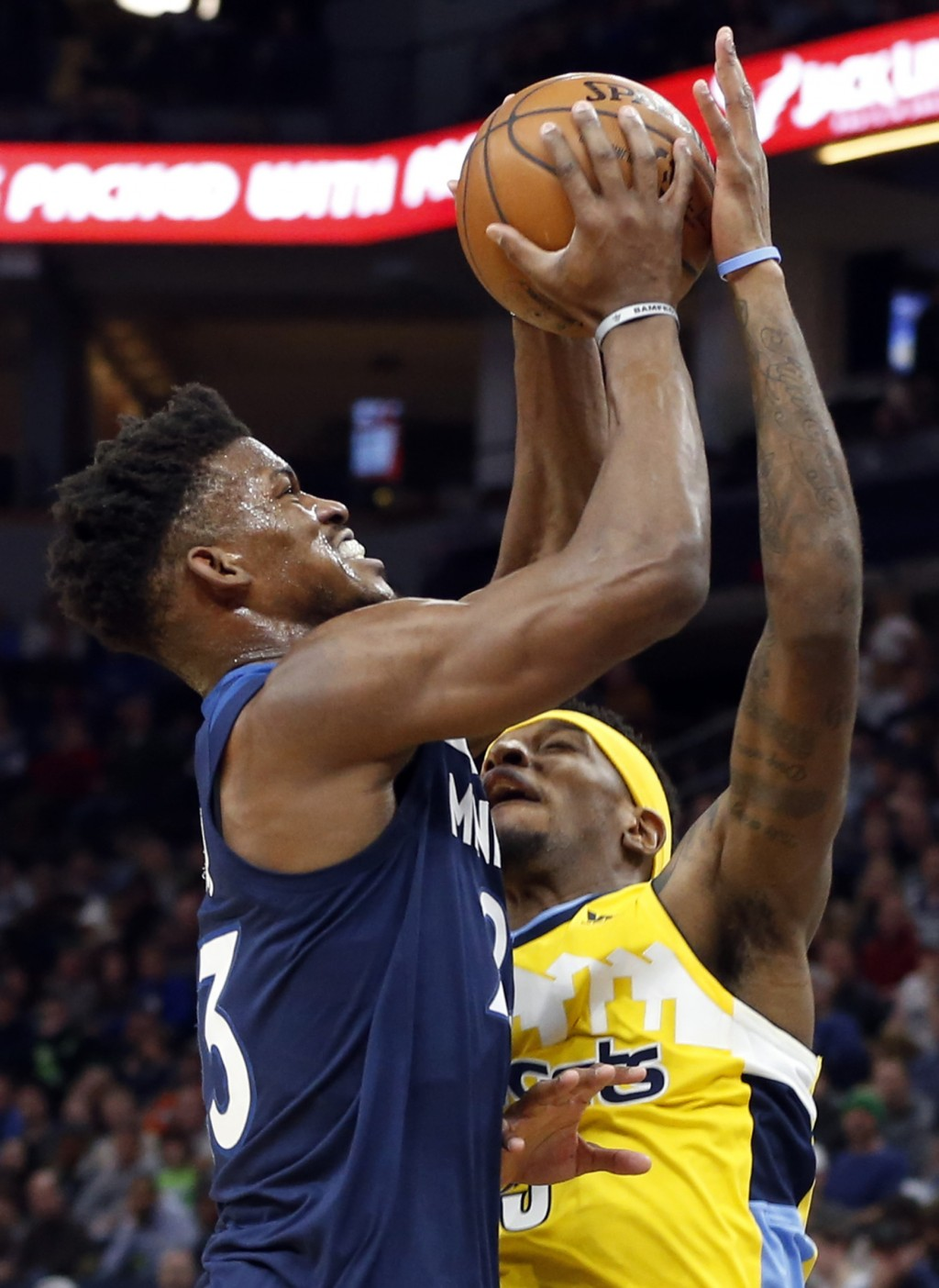 Minnesota Timberwolves' Jimmy Butler, left, attempts a shot as Denver Nuggets' Torrey Craig reaches up to block the ball in the first half of an NBA b...
