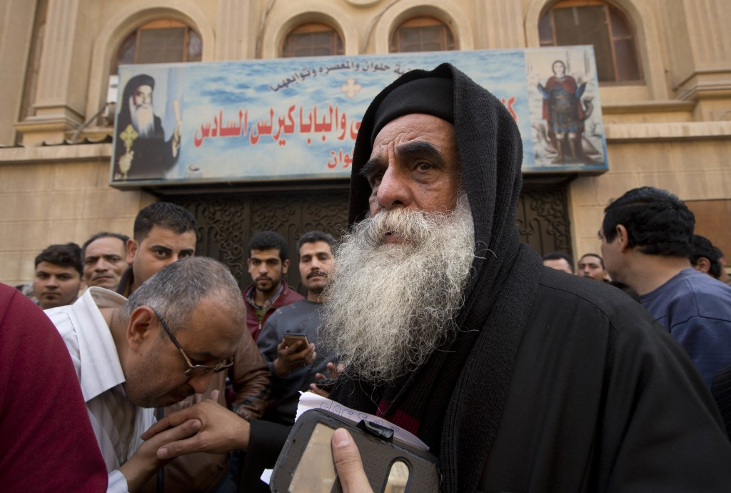 Priest David, the head of Mar Mina church, is greeted by people outside the chruch, in Helwan, Cairo, Egypt, Friday, Dec. 29, 2017, where at least 10 ...