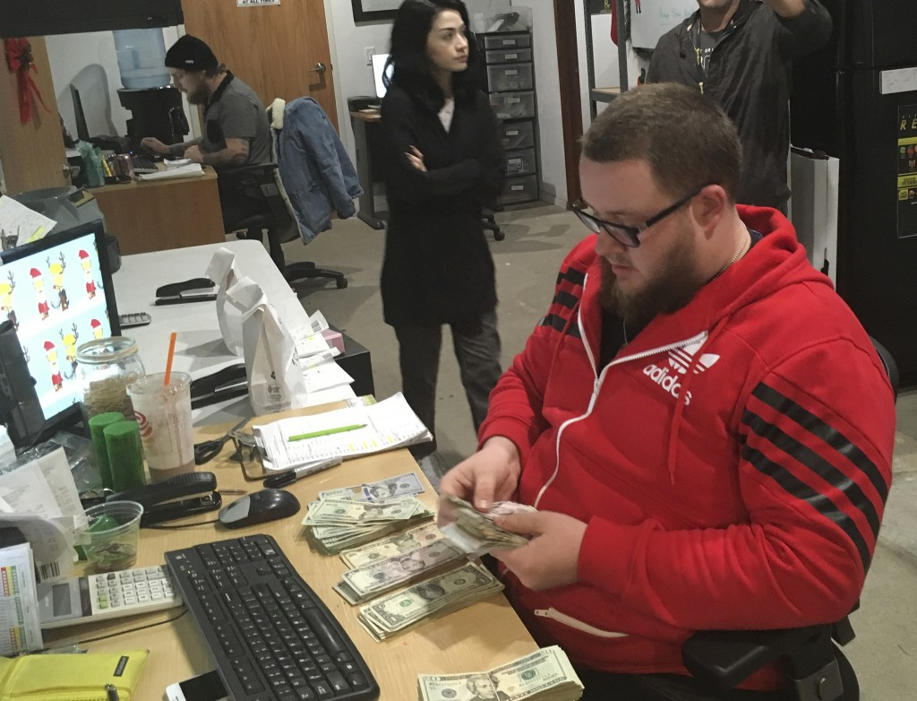 In this Wednesday, Dec. 27, 2017, photo Employee Joshua Wilson counts cash at the Golden State Greens marijuana dispensary in San Diego. A few dozen C...