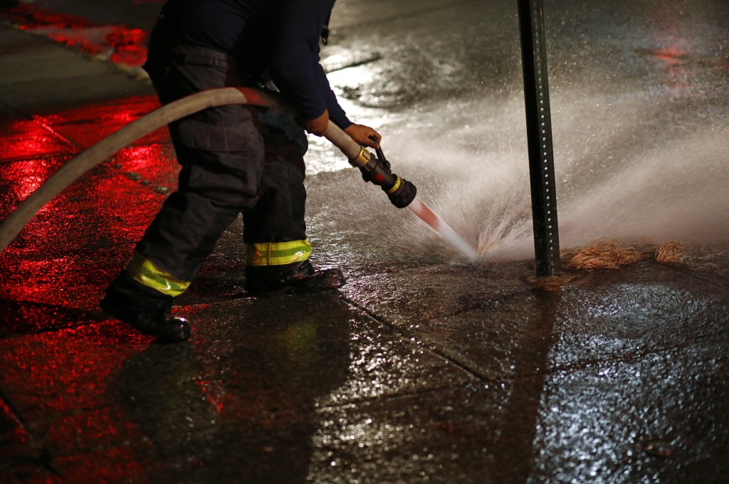 In this Dec. 14, 2017 photo, a member of the Baltimore Fire Department washes away blood stains that were left behind at a homicide scene in Baltimore...
