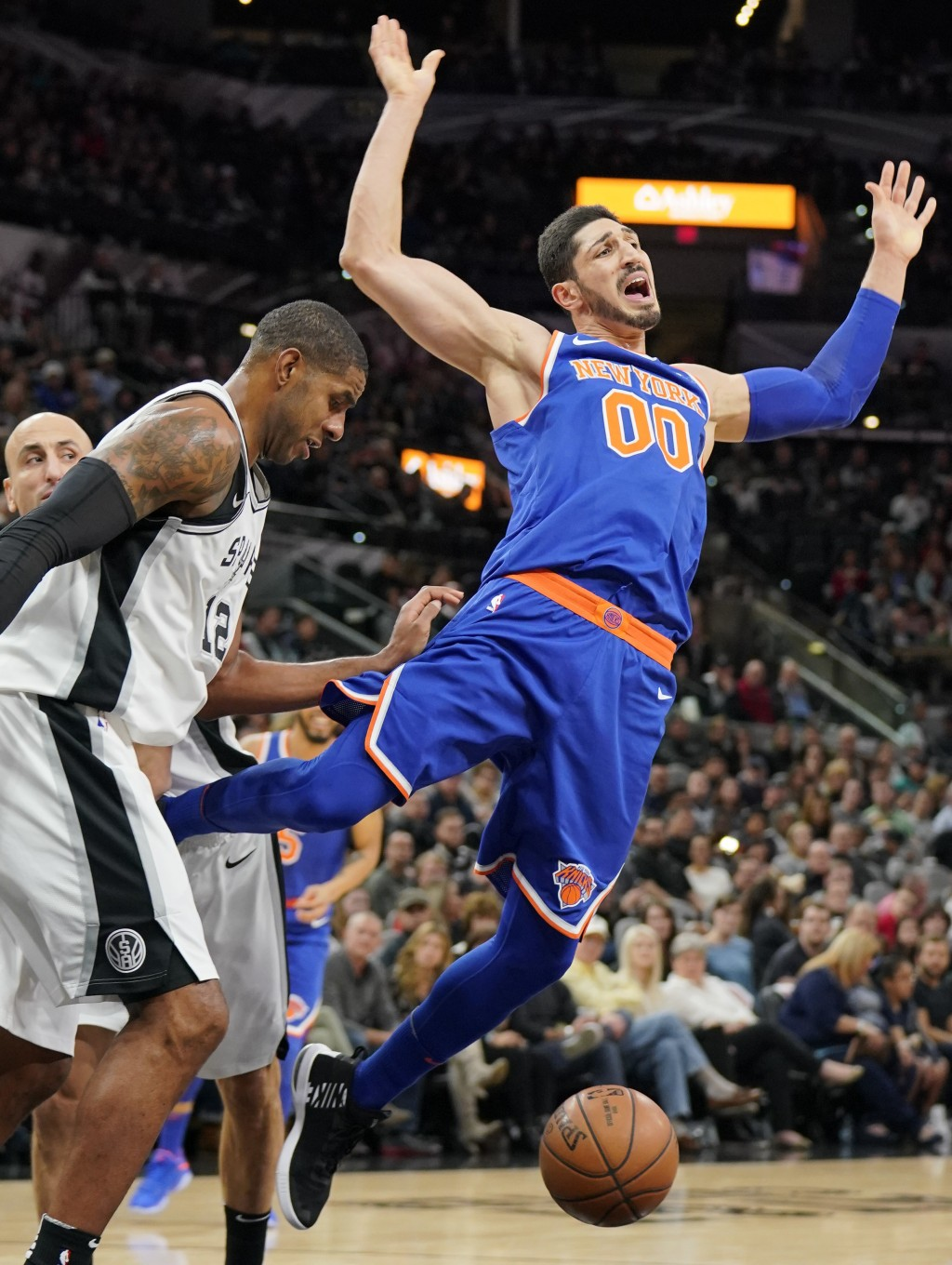 New York Knicks' Enes Kanter (00) falls after losing the ball to San Antonio Spurs' LaMarcus Aldridge during the first half of an NBA basketball game ...