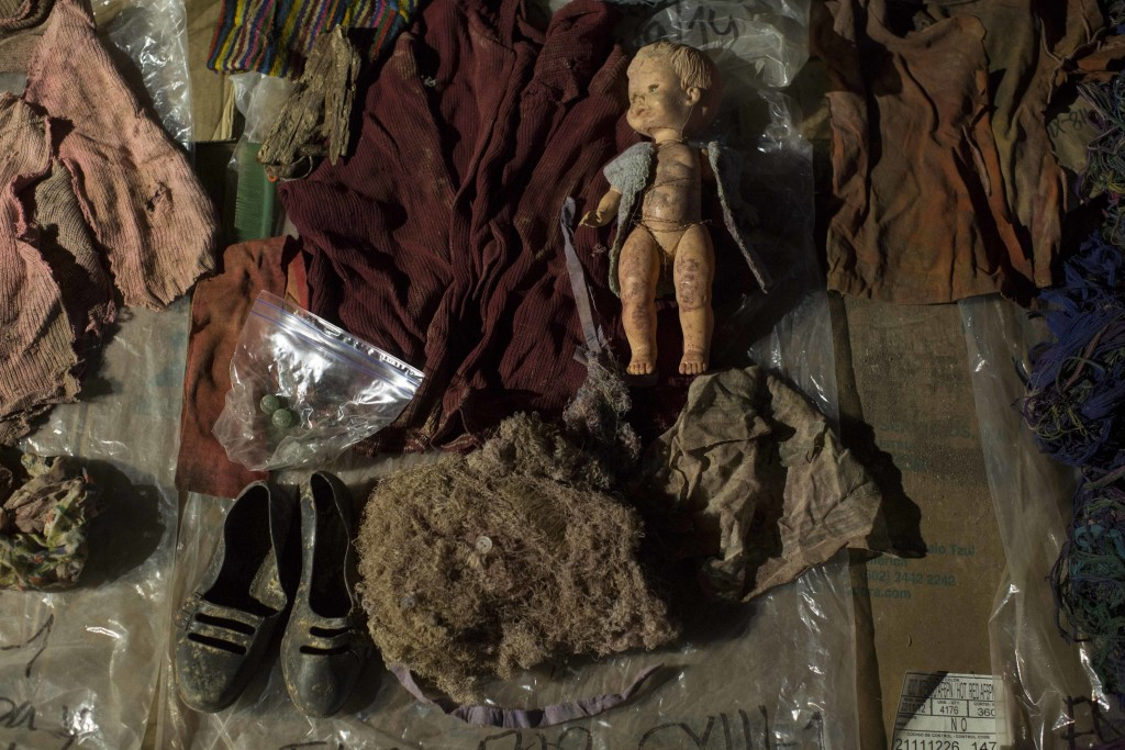 In this Nov. 29, 2017 photo, clothing, earrings and a doll that were found among the remains of over 100 Ixil Mayans exhumed from a mass grave, lay on...