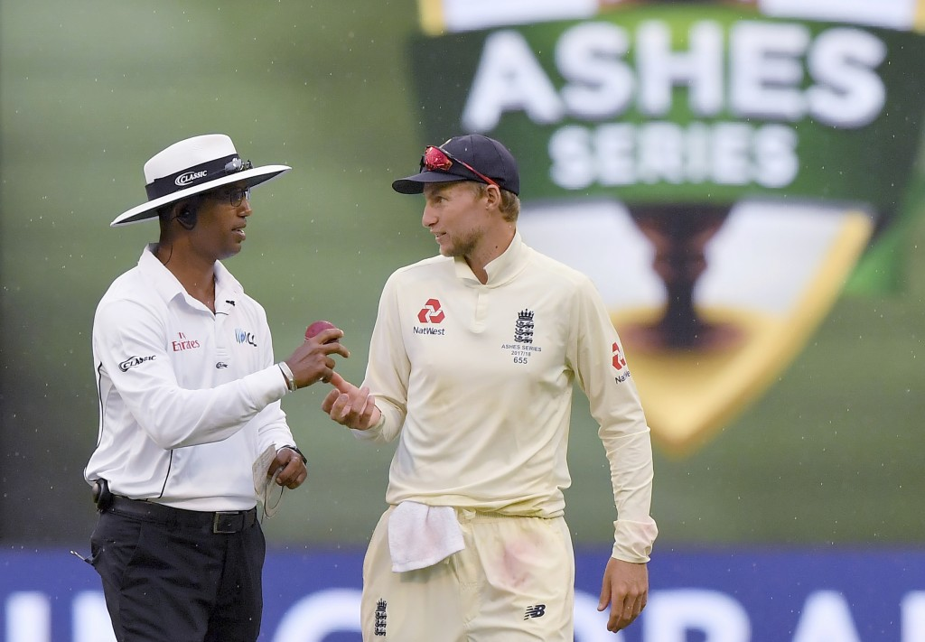 England's Joe Root, right, talks with umpire Kumar Dharmasena as rain interrupts play during the fourth day of their Ashes cricket test match against ...