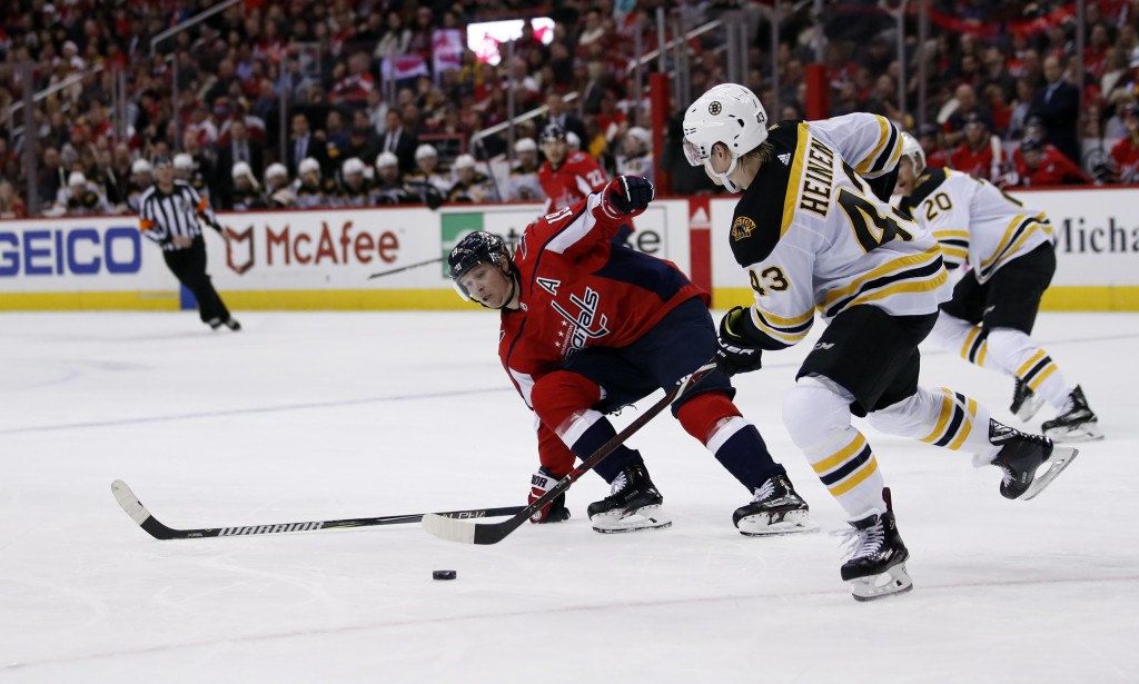 Boston Bruins center Danton Heinen (43) tries to pass the puck past Washington Capitals center Nicklas Backstrom (19), from Sweden, during the second ...