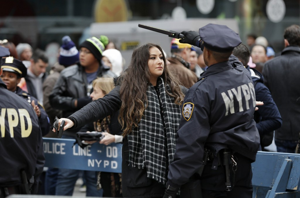 FILE - In this Dec. 31, 2015 file photo, pedestrians submit to a search as they enter Times Square in New York. New York Police Department officials s...